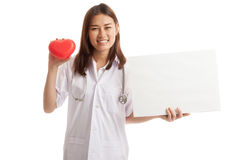 Young Asian female doctor with red heart and blank sign. Young Asian female doctor with red heart and blank sign isolated on white background stock photo