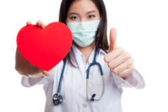 Young Asian female doctor with red heart. Young Asian female doctor with red heart isolated on white background stock image