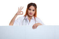 Young Asian female doctor show OK sign  behind blank white billb Royalty Free Stock Photos