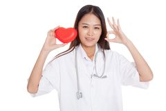 Young Asian female doctor show OK sign with red heart. Isolated on white background royalty free stock image