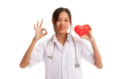 Young Asian female doctor show OK sign with red heart. Isolated on white background royalty free stock photography