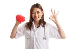 Young Asian female doctor show OK sign with red heart. Young Asian female doctor show OK sign with red heart isolated on white background stock photo