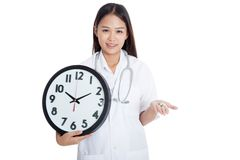 Young Asian female doctor smile with a clock and pills in hand Stock Images