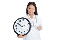 Young Asian female doctor smile with a clock and pills Stock Images