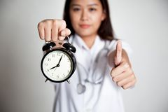 Young Asian female doctor thumbs up with a clock Stock Photos