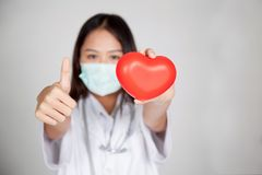 Young Asian female doctor  thumbs up with red heart Stock Photos