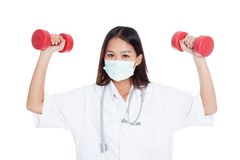 Young Asian female doctor wear mask with dumbbell in both hands Stock Photos