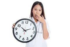 Young Asian female doctor yawn with a clock Stock Images