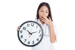 Young Asian female doctor yawn with a clock Stock Photos