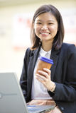Young Asian female executive drinking coffee and using laptop PC Stock Image