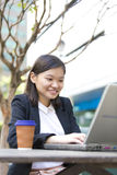 Young Asian female executive drinking coffee and using laptop PC Royalty Free Stock Photography