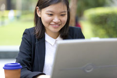 Young Asian female executive drinking coffee and using laptop PC Royalty Free Stock Photo