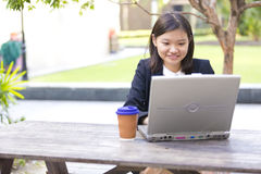 Young Asian female executive drinking coffee and using laptop PC Royalty Free Stock Photos