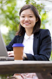Young Asian female executive drinking coffee and using laptop PC Stock Images