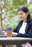 Young Asian female executive drinking coffee and using laptop PC Stock Photography