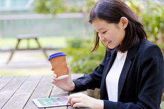 Young Asian female executive drinking coffee and using tablet PC Stock Image
