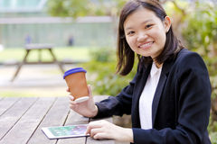 Young Asian female executive drinking coffee and using tablet PC Stock Photos