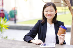 Young Asian female executive drinking coffee and using tablet PC. Smiling Royalty Free Stock Images