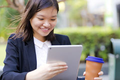 Young Asian female executive drinking coffee and using tablet PC Royalty Free Stock Photography