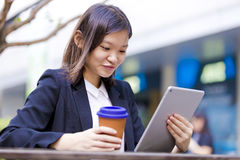 Young Asian female executive drinking coffee and using tablet PC Stock Photo