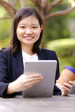 Young Asian female executive drinking coffee and using tablet PC Stock Photography