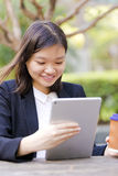 Young Asian female executive drinking coffee and using tablet PC Royalty Free Stock Photo
