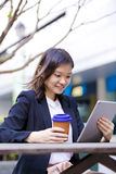 Young Asian female executive drinking coffee and using tablet PC Royalty Free Stock Image