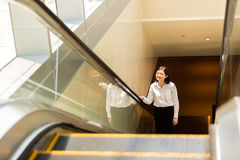 Young Asian female executive going up escalator Royalty Free Stock Photos