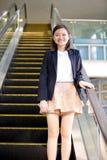 Young Asian female executive going up escalator Stock Photos