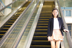 Young Asian female executive going up escalator Royalty Free Stock Image