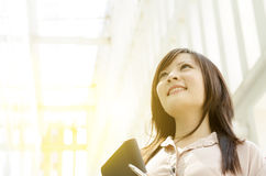 Young Asian female executive looking up. Young Asian business woman smiling and looking up, standing in an office environment, beautiful golden sunlight at Royalty Free Stock Images