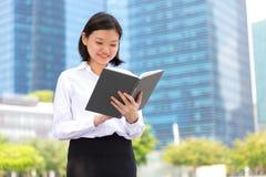 Young Asian female executive reading book Stock Photos