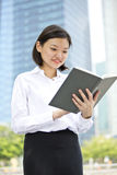 Young Asian female executive reading book and smiling Royalty Free Stock Images