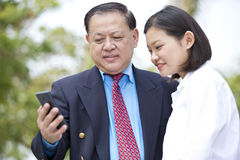 Young Asian female executive and senior businessman using smart phone Stock Photo