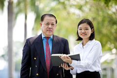 Young Asian female executive and senior businessman walking together Stock Photography