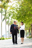 Young Asian female executive and senior businessman walking together Stock Image