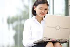 Young Asian female executive using laptop Stock Photography