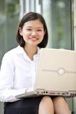 Young Asian female executive using laptop Stock Photos