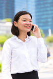 Young Asian female executive using smart phone and smiling Stock Photography