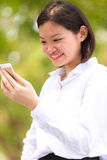 Young Asian female executive using smart phone and smiling Royalty Free Stock Photo