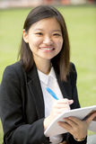 Young Asian female executive writing on notepad Royalty Free Stock Image