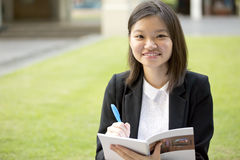 Young Asian female executive writing on notepad Royalty Free Stock Photos