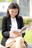 Young Asian female executive writing on notepad Stock Image
