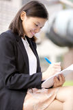 Young Asian female executive writing on notepad Royalty Free Stock Images