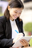 Young Asian female executive writing on notepad Stock Photo