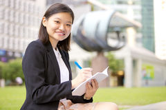 Young Asian female executive writing on notepad Stock Images