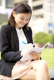 Young Asian female executive writing on notepad Stock Photos