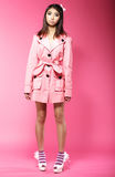 Young Asian Female Fashion Model in Pink Coat standing in Studio Royalty Free Stock Photography