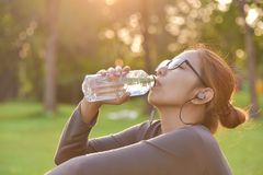 Asian female is resting and drinking water. royalty free stock image