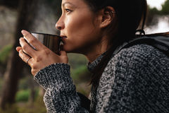 Young asian female hiker drinking coffee. Close up side shot of young asian female hiker drinking coffee. Female hiker taking rest during hike Royalty Free Stock Photo